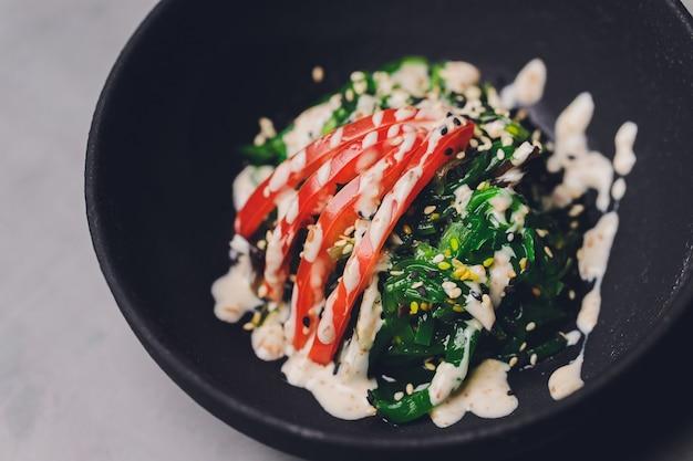 Close-up van chuka-salade geserveerd in een witte kom, verticaal schot, donkere bruine steenachtergrond.