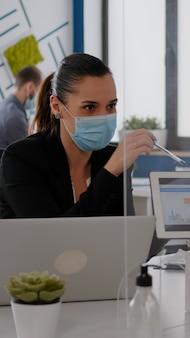 Close up van collega's met gezichtsmasker die samenwerken bij financieel project met behulp van tabletcomputer whi