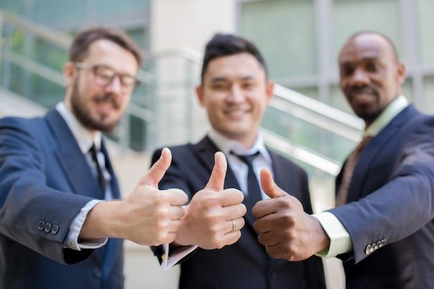 Close-up van commercieel team dat hun duimen tegenhoudt
