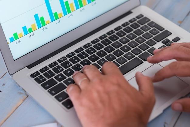 Close-up van computer of laptop en papier met statistieken over een blauwe tafel van hout met de handen van een man op de foto - blauwe tafel van hout -