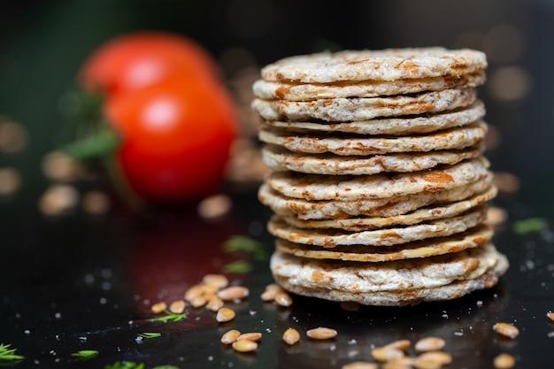 Close-up van crackers bovenop elkaar op de tafel met groenten onder de lichten