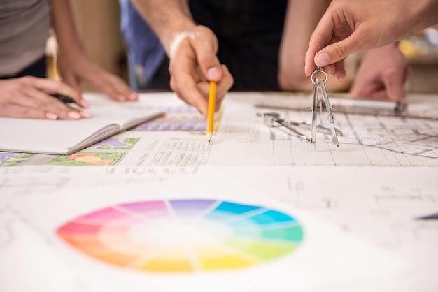 Close-up van creatieve architecten die bij ontwerp in bureau werken.