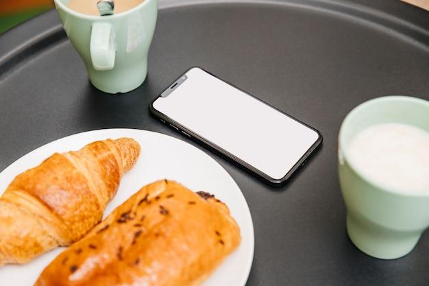 Close-up van croissants, melk en mobiele telefoon bij het ontbijt