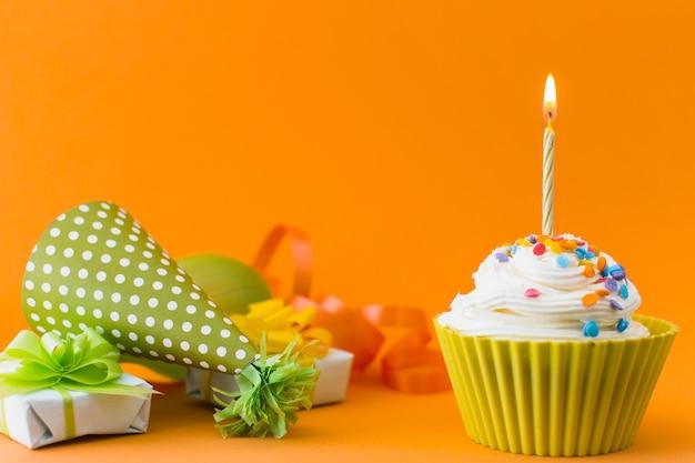 Close-up van cupcake dichtbij giften en deelhoed op oranje achtergrond