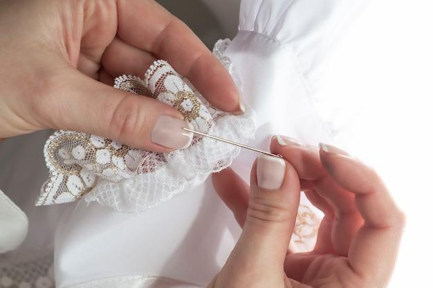 Close up van dames handen met een naald en gouden kant
