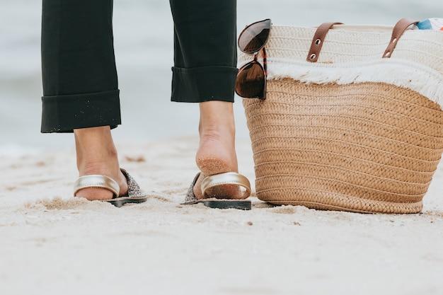 Close-up van de achterkant van de voeten van een vrouw met een strandtas in de buurt en een zonnebril