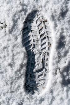 Close-up van de afdruk van schoenen in de sneeuw. enkele duidelijk gedefinieerde voetafdruk van een schoen in de sneeuw. winter en seizoenen concept