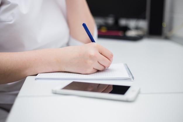 Close-up van de arts die in een notitieboekje aan het bureau op kantoor schrijft