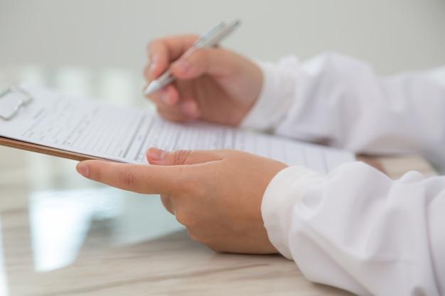 Close-up van de arts met behulp van het klembord en pen