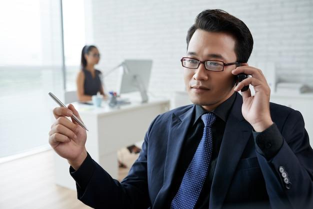 Close-up van de aziatische mens die op de telefoon in het bureau spreekt