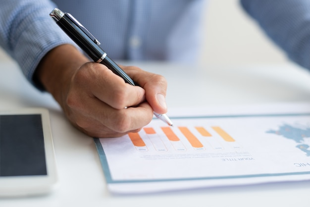Close-up van de bedrijfsmens die diagram bestudeert