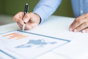 Close-up van de bedrijfsmens die grafiek analyseren