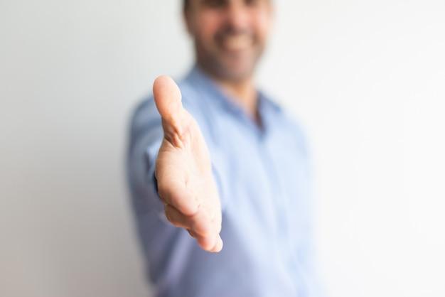 Close-up van de bedrijfsmens die hand voor handdruk aanbiedt