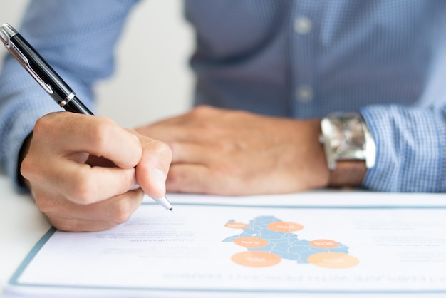 Close-up van de bedrijfsmens die kaartgrafiek bestudeert