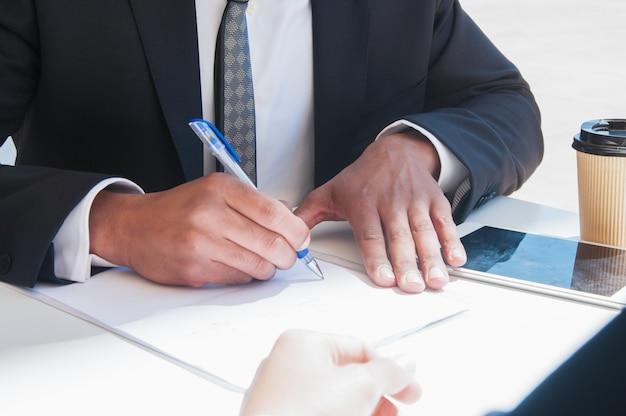 Close-up van de bedrijfsmens die op document blad bij lijst schrijft