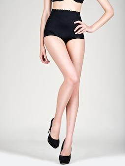 Close-up van de benen van de jonge vrouw in zwarte schoenen met hoge hakken