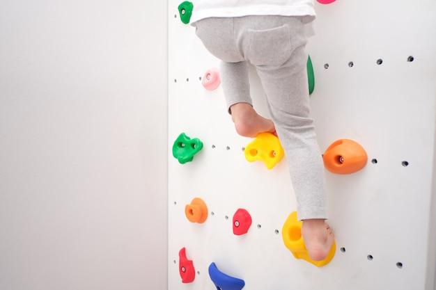 Close-up van de benen van de kleine jongen van de kleuterschool die plezier probeert te klimmen op een kleine rotswand binnenshuis