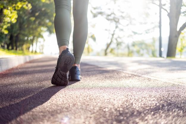 Close-up van de benen van de vrouw in sport sneakers lopen in het park op zonsopgang tijd gezonde fitness levensstijl