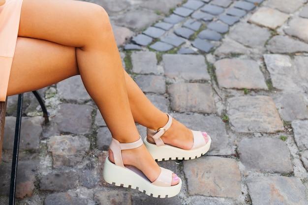 Close-up van de benen van een meisje die zittend op een bankje mooie witte sandalen