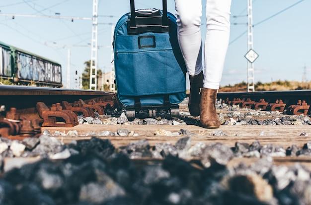Close-up van de benen van een vrouw die met haar koffer langs een spoorlijn loopt.