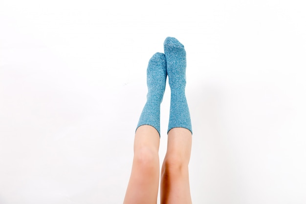 Close-up van de blote benen van een jonge vrouw die blauwe sokken met zijn voeten draagt.