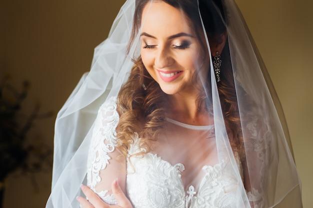 Close-up van de bruid met bruidssluier en huwelijkstoga.