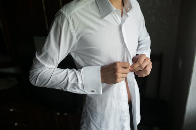 Close-up van de bruidegom dichtknopen zijn hemd