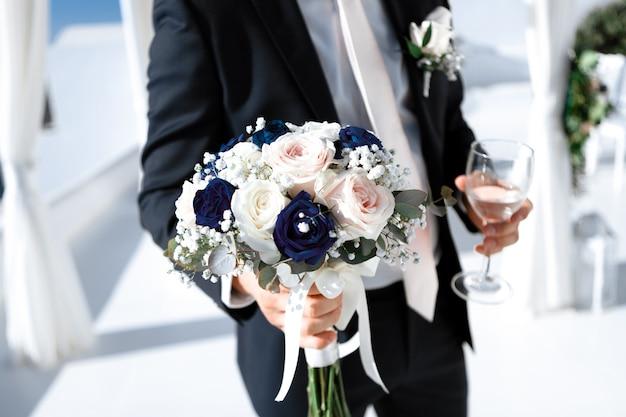 Close-up van de bruidegom in een elegant kostuum met een boeket van de bruid en een glas lichte wijn, selectieve nadruk