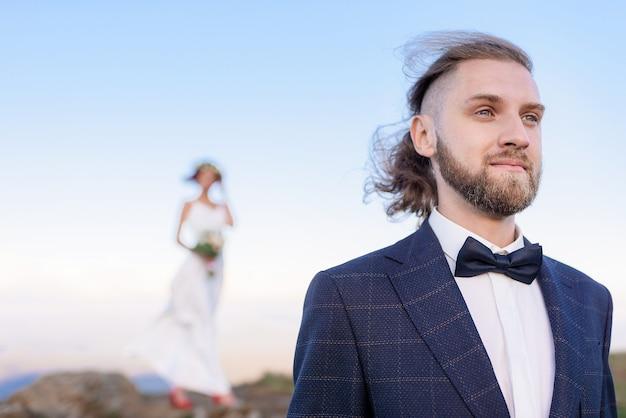 Close-up van de bruidegom is in focus vooraan en de bruid is onscherp achter