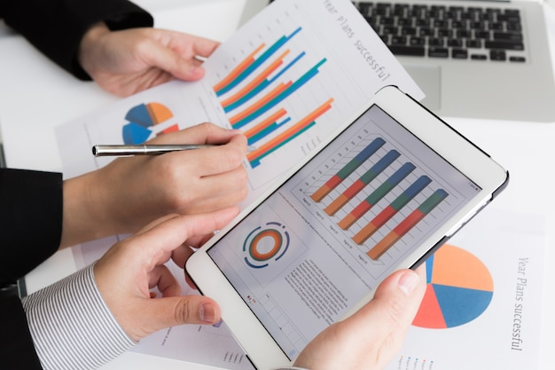 Close-up van de business team met behulp van digitale tablet met financiële d