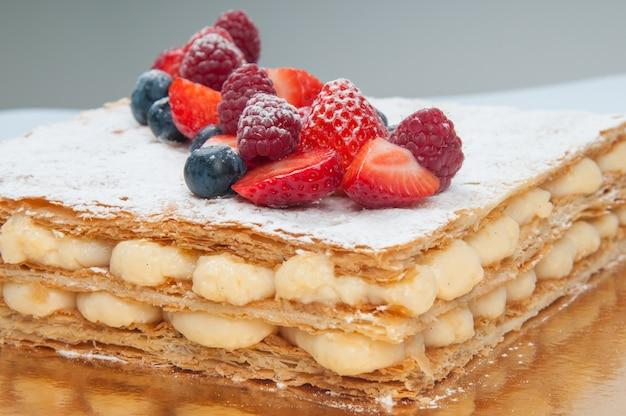 Close-up van de cake van de bladerdeeglaag die met verse bessen wordt verfraaid