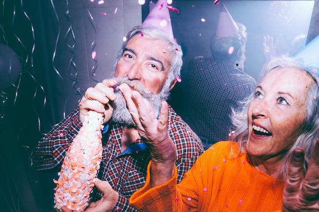 Close-up van de champagnefles van de hogere mensenholding en haar vrouw die confettien in lucht werpen bij verjaardagspartij