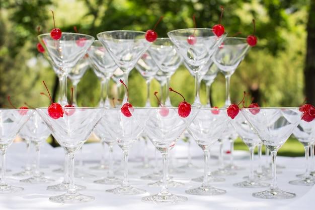 Close-up van de champagnepiramide met een rode kers aan de bovenkant van elk glasglazen bekers. piramide van champagne. een feestelijk drankje. decoraties voor het banket.