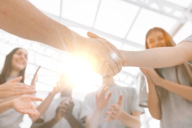 Close up van de deelnemers aan de briefing die elkaar de hand schudden