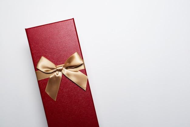 Close-up van de doos van de kerstmisgift van rode kleur met gouden boog, die op witte achtergrond met exemplaarruimte wordt geïsoleerd.