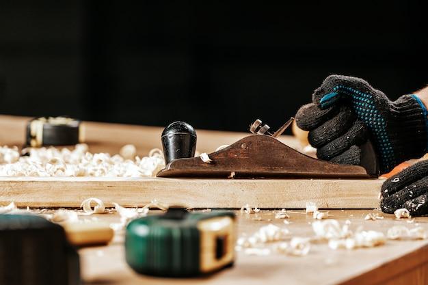 Close-up van de een jonge man-bouwer behandelt een houten bar met een krikvliegtuig in de werkplaats