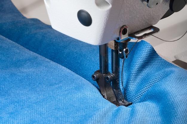 Close-up van de elektrische huishoudnaaimachine en het kledingstuk.