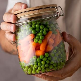 Close-up van de erwten en de babywortelen van de persoonsholding in glazen pot