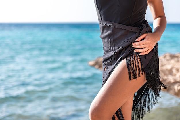 Close-up van de gebruinde benen van een meisje in de buurt van de zee.