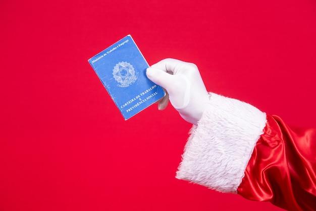Close-up van de gehandschoende hand van de kerstman die een braziliaanse werkkaart vasthoudt.