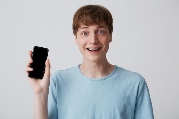 Close-up van de gelukkige knappe jonge man met beugels aan de tanden draagt een blauw t-shirt