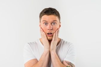 Close-up van de geschokte jonge man met zijn hand op de wangen tegen een witte achtergrond