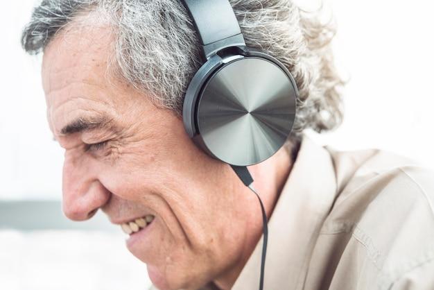 Close-up van de glimlachende hogere mens die van muziek op hoofdtelefoon geniet