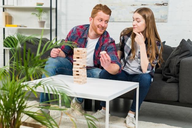 Close-up van de glimlachende jonge mens die het verwijderde houten blok van toren aan haar meisje toont