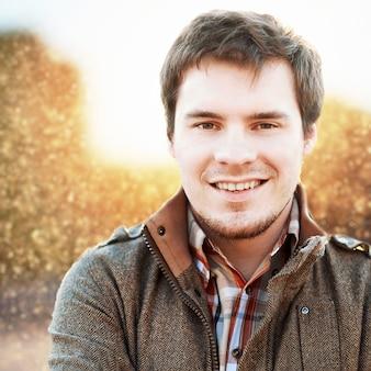 Close-up van de glimlachende man in het veld bij zonsondergang