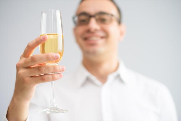 Close-up van de glimlachende mens die drinkbeker met champagne opheft