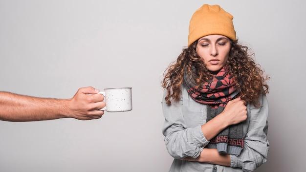 Close-up van de hand aanbieden van koffie aan zieke vrouw met verkoudheid en griep