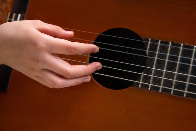 Close-up van de hand akoestische gitaar spelen.