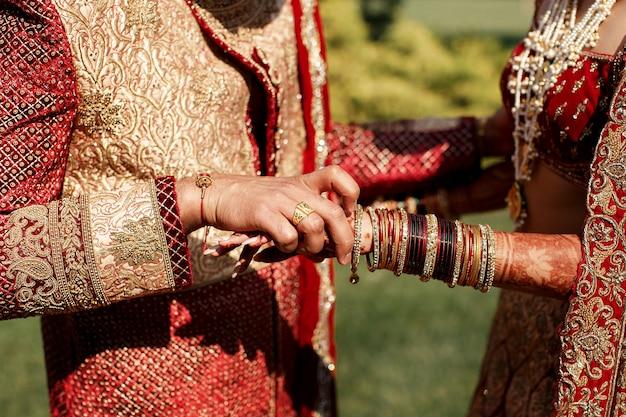 Close-up van de hand die van de bruidegom de armband van het eerste opstijgt
