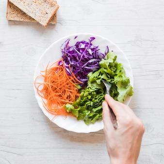Close-up van de hand die van de persoon plantaardige salade met lepel op houten bureau neemt